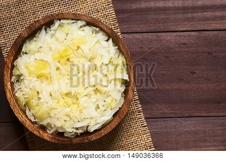 Sauerkraut in wooden bowl photographed overhead on dark wood with natural light (Selective Focus Focus on the top of the sauerkraut)