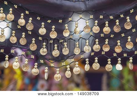 Black laid out scarf with golden coins hanging for belly dancing