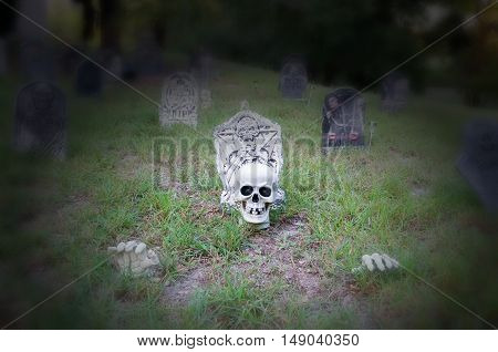 Skull in ground surrounded by tombstones in a yard