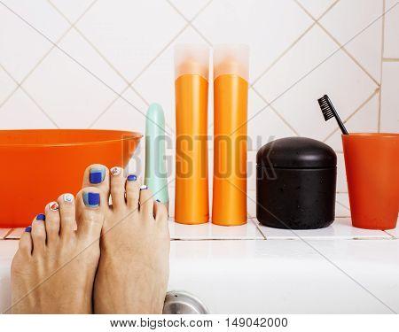 woman legs in bathroom with lot of stylish stuff for care, pedicure creative design, hygiene spa mani pedi concept