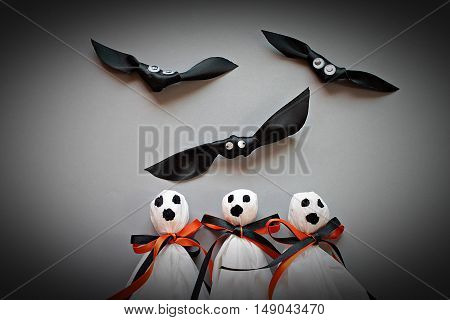Halloween concept background : Three halloween ghosts DIY made from white tissue paper, black and orange ribbon and three bats DIY made form black ribbon on gray background