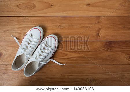 Youth white sneakers with white untied the laces on wooden background