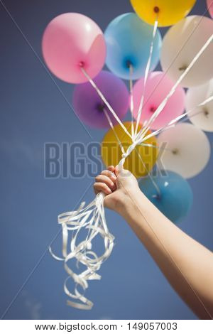 Vintage tone of person holding multi colored helium ballons. Focus at hand
