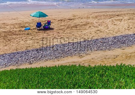 chair and umbrella on a lonely beach