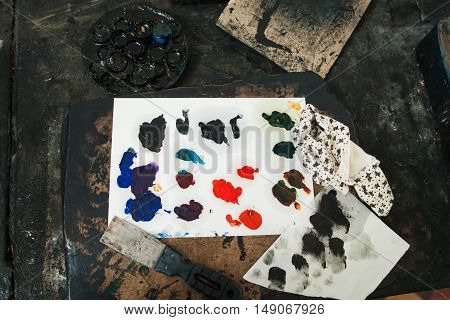 Palette with palette-knife and rag, flat lay. Top view on artist workplace with art tools for painting picture. Hobby, talent, occupation, craft concept.