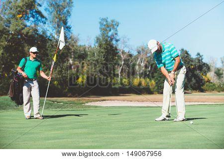 Detail from golf game: making a final putt