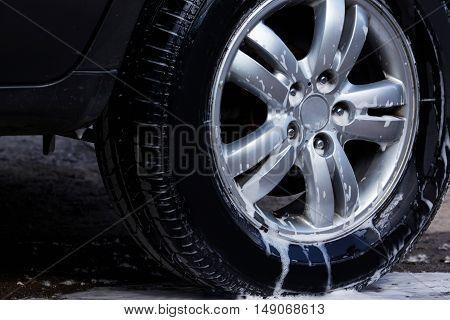 car wheel is washing in soap suds