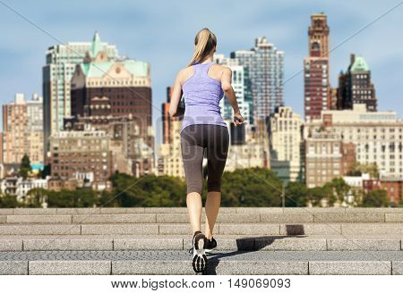 Rear view of a slim woman running up stairs on a sunny day. The background shows the blurred skyline of Brooklyn New York.