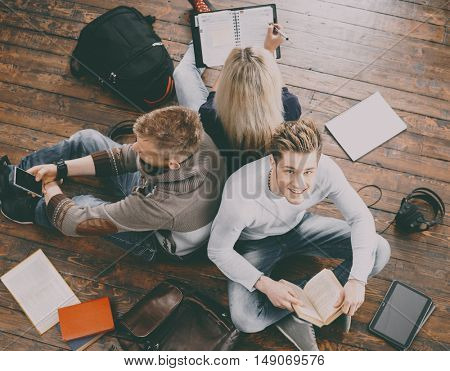 Group of students reading books, writing in notebooks and using a smartphone leaning on each other on wooden floor.