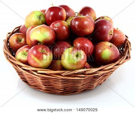 Basket with red apples on white background