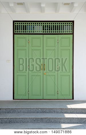 Green wooden door Thai traditional style on white cement wall
