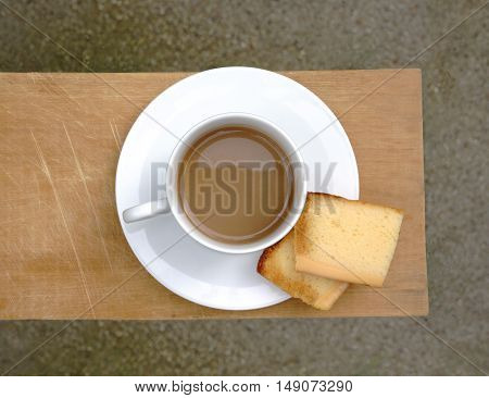 Cup of Coffee witch cake on wooden board