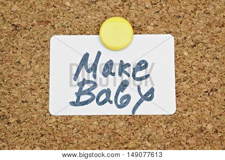 Text Make Baby and white sticker pinned on a cork panel
