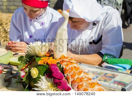 Zaporizhia/Ukraine- September  17, 2016: Family festival of homemade pickled canned vegetables and preserves. Peacock figure carved from zucchini decorated by carrot elements. Culinary school students participating at vegetables carving workshop.