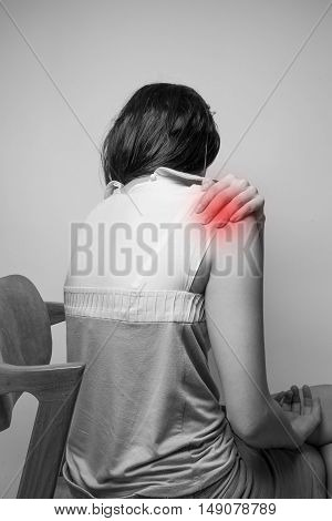 a woman have a shoulder pain in black and white
