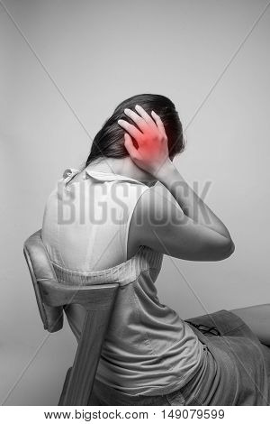 Woman suffering from a headache grimacing and holding her hands to her ears to relieve the throbbing
