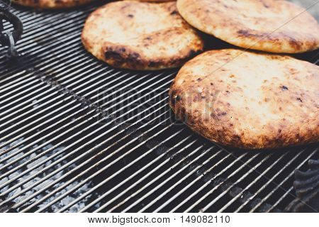Several pitas closeup on barbecue outdoors. Middle eastern home made freshly baked bread on large bbq grill. Country fair food sale for picnic