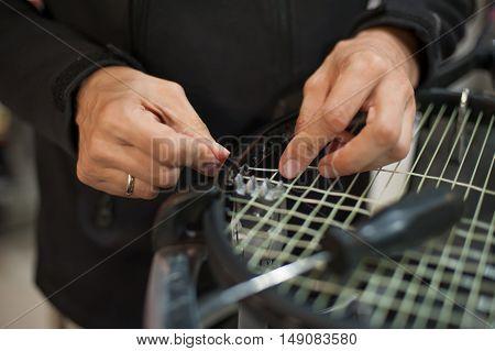 Close Up Of Tennis Stringer Hands Doing Racket Stringing
