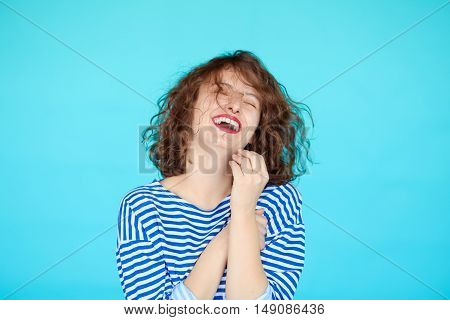 portrait of laughing hipster teenage girl against blue color background. Happy young woman in striped clothes in marine style isolated