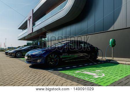 TILGURG, NETHERLANDS - SEPTEMBER 25, 2016:  Black Tesla Model S electric car is being charged at Tesla Supercharger Station of Tilburg, Netherlands.