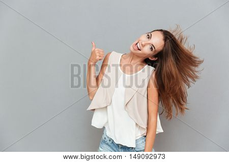 Portrait of a cheerful casual woman showing thumbs up isolated on a gray background