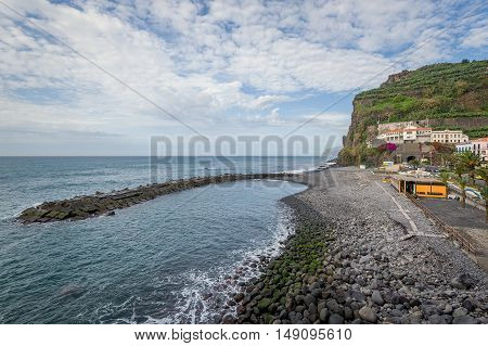 Ponta do Sol small town bay with stone pier and beach line. Madeira island, Portugal