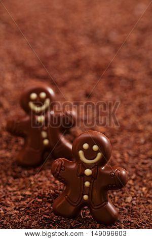 dark chocolate gingerbread man on chocolate flakes background