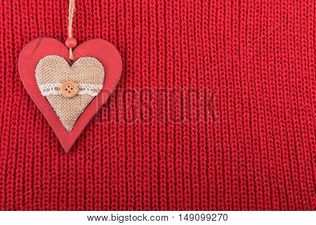 Christmas wooden decoration heart on red wool fabric. Christmas rustic background with copy space.