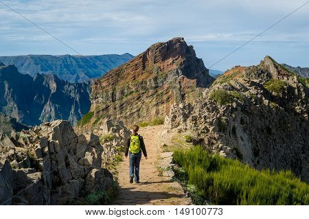 Woman hiker with green backpack doing her hike of Pico Arieiro to Pico Ruivo hiking route. Madeira island, Portugal.