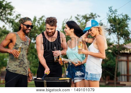 Group of happy young people standing and frying meet on barbeque grill outdoors