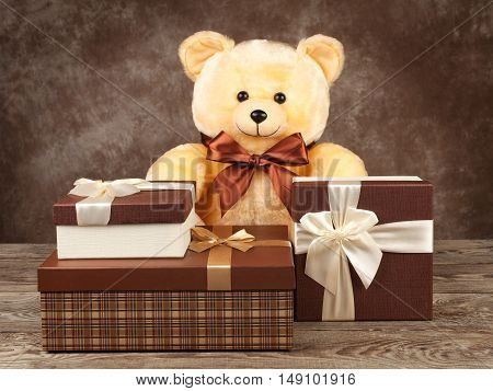homemade teddy bear and a lot of boxes with gifts on the old board