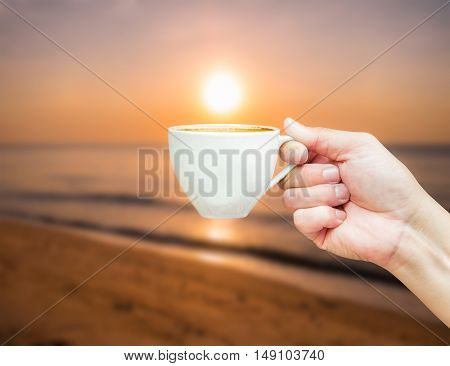 Hot coffee cup in hand with blur background of sunset on the beach.