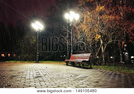 Autumn rainy night. Autumn landscape of night autumn park. Autumn rainy night with lonely bench under falling autumn rain -night autumn landscape. Night in autumn city park. Autumn night landscape