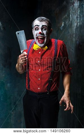The crazy clown holding a knife on dack. Halloween concept of horror and murderer
