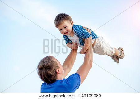 Man toss the boy up. Behind Ocean and clean sandy beach