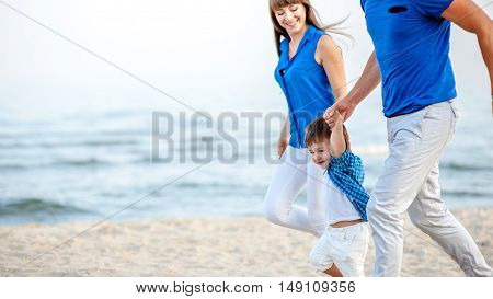 Man woman and child run on the beach near the ocean and feel happy