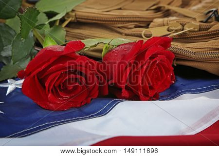Red roses on American flag with military backpack, closeup