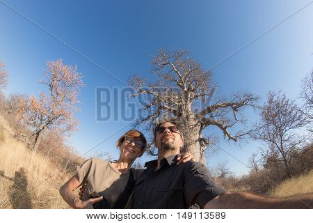 Couple taking selfie near Baobab plant in the african savannah with clear blue sky. Fisheye view from below. Wilderness safari and adventure in Africa.