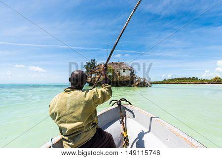 arfican on the boat sailing to the Rock restaurant in ocean on the horizon, Zanzibar
