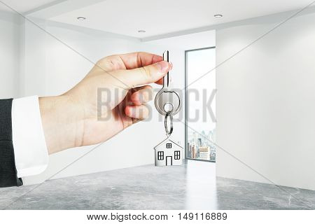 Closeup of businessman hand holding key with house keychain in concrete interior. Real estate and mortgage concept