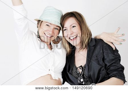 Close up lifestyle portrait of two attractive fancy friends in hipster fashionable outfit . isolated with light background.
