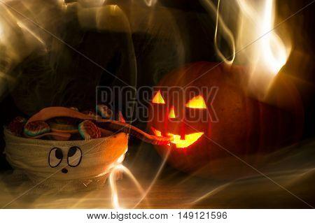 Halloween pumpkin head jack lantern eating mummy brains in mistery smoke. funny halloween background