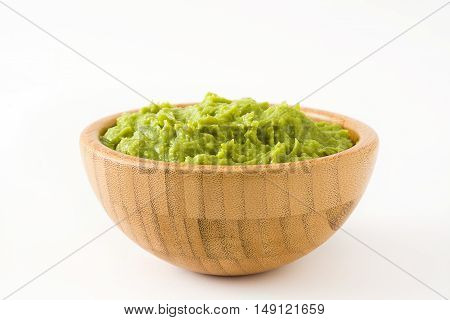 Guacamole in a wooden bowl isolated on white background