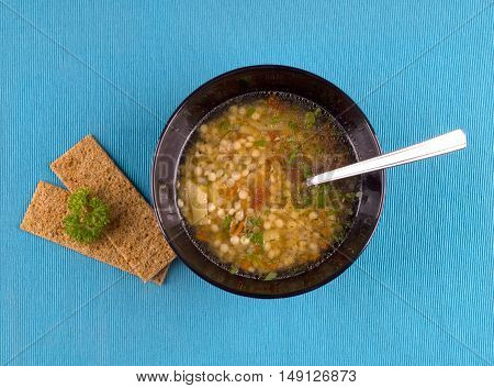 Lentil soup with herbs in black mask on a blue background. Lentil soup with pasta and loaves on it.