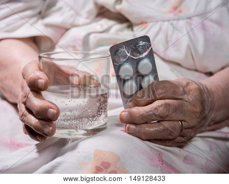 Old Sad Woman Holding Pills