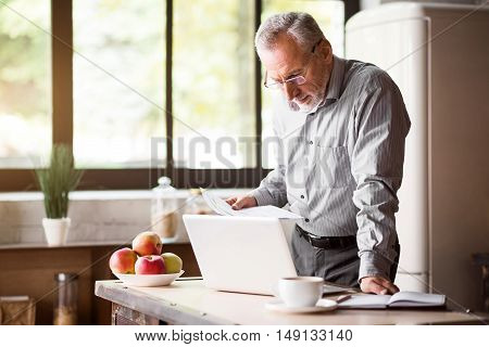 Business in the morning. Good-looking grey enterpreneur in glasses working with laptop and papers while having coffee and breakfast