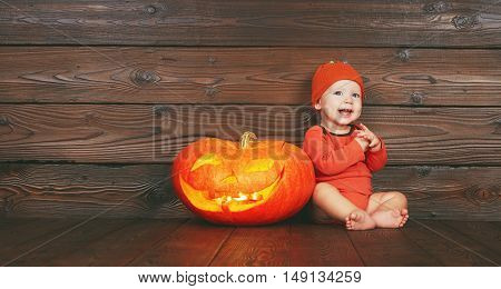 Halloween. Happy funny baby with a pumpkin jack on a wooden background