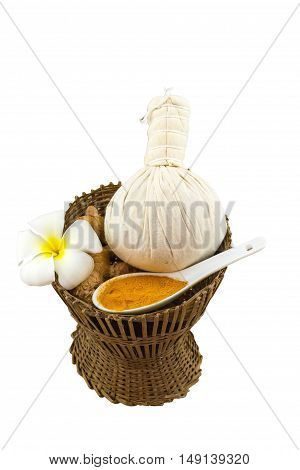 Spa herbal compressing ball white frangipani flowers (Plumeria spp Apocynaceae Pagoda tree Temple tree) turmeric powder in white spoon and candle in bamboo basket on brown fabric sack background