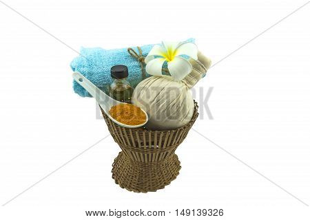 Spa herbal compressing ball white frangipani flowers (Plumeria spp flower Apocynaceae flower Pagoda tree flower Temple tree flower) turmeric powder in white spoon massage oil and blue faric on bamboo basket isolate on white background.Saved with clipping