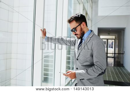 Confident man boss in luxury suit is checking e-mail via cellphone before meeting with staff. Male professional employer is typing text message on mobile phone while is standing in airport hallway